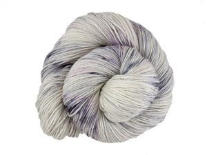 A close up of a white and soft grey with speckles of black and purple coloured skein of superwash bluefaced leicester, silk and cashmere 4ply fingering sock yarn presented as a spiral on a white background (Newsprint on Blue Chip Stocking)