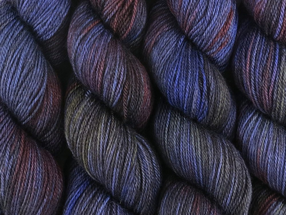 A close up of variegated deep blue, charcoal, violet, blood red and hints of straw yellow coloured skeins of superwash bluefaced leicester, silk and cashmere 4ply fingering sock yarn (Night's Watch on Blue Chip Stocking)