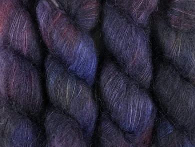 A close up of variegated deep blue, charcoal, violet, blood red and hints of straw yellow coloured skeins of superfine kid mohair and silk 2ply lace yarn (Night's Watch on Kid Glove Lace)