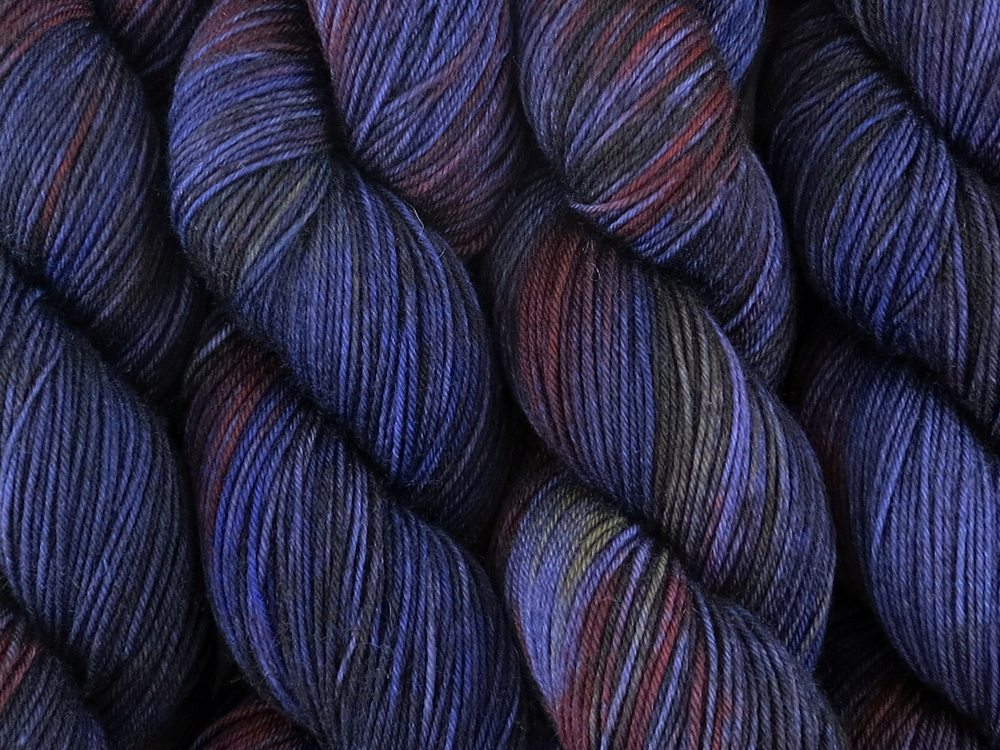 A close up of variegated charcoal, deep blue, violet and red with hints of yellow coloured skeins of superwash merino and nylon 4ply fingering sock yarn (Night's Watch on Tough Stocking)