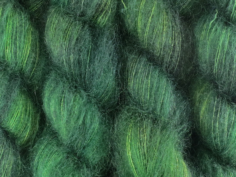 A close up of semi-solid deep green with hints of charcoal, emerald, chartreuse and kelly green coloured skeins of superfine kid mohair and silk 2ply lace yarn (Nori on Kid Glove Lace)