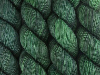 A close up of semi-solid deep green with hints of charcoal, emerald, chartreuse and kelly green coloured skeins of superwash merino and nylon 4ply fingering sock yarn (Nori on Tough Stocking)