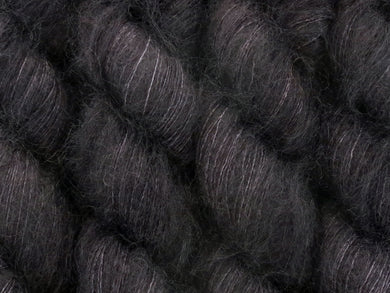 A close up of almost solid true black coloured skeins of superfine kid mohair and silk 2ply lace yarn (Pitch Black on Kid Glove Lace)