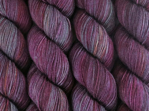 A close up of variegated purple, maroon, orange and mint green coloured skeins of superwash merino and nylon 4ply fingering sock yarn (Purple Smoke Bush on Tough Stocking)