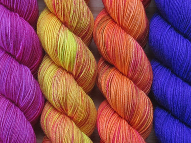 A close up of four skeins of yarn from left to right: tonal bright pinks; yellow with hints of lime green and pink red speckles; oranges with hints of pink and moss green; and tonal deep purple (Queen of Sheba Caladenia MKAL Yarn Kit on Silk Stocking)