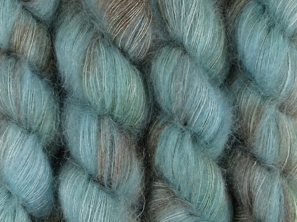 A close up of variegated blue, aqua, brown with hints of kelly green coloured skeins of superfine kid mohair and silk 2ply lace yarn (Rockpool on Kid Glove Lace)