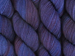 A close up of semi-solid dark blue, midnight blue, deep red-purple and maroon coloured skeins of superwash merino and nylon 4ply fingering sock yarn (Round Midnight on Tough Stocking)
