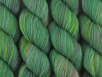 A close up of variegated light grey-green with hints of pink, sulphur yellow and deep jade green coloured skeins of superwash merino and nylon 4ply fingering sock yarn (Samphire on Tough Stocking)
