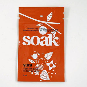One dark orange sachet of Soak rinse-free laundry liquid on a white background (Yuzu scent)