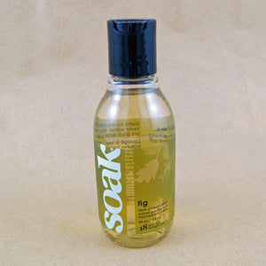 One small bottle of Soak rinse-free laundry liquid with a green label, on a tan background (Fig scent)