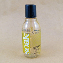 Load image into Gallery viewer, One small bottle of Soak rinse-free laundry liquid with a yellow label, on a tan background (Pineapple Grove scent)
