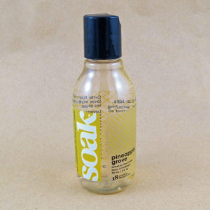 One small bottle of Soak rinse-free laundry liquid with a yellow label, on a tan background