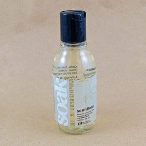 One small bottle of Soak rinse-free laundry liquid with a white label, on a tan background (Scentless)