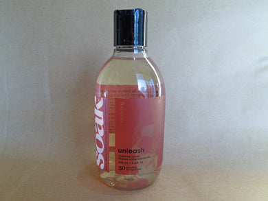 One bottle of Soak rinse-free laundry liquid with an orange pink label, on a tan background (tenth anniverasry second release of the Unleash scent)