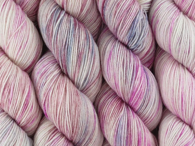 A close up of variegated white, pink, grey, silver and maroon coloured skeins of superwash merino and nylon 4ply fingering sock yarn (Steel Magnolia on Tough Stocking)