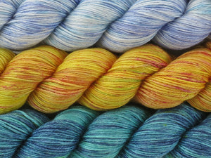 A close up of three variegated skeins of yarn from white with blues and teal at the top to yellow with hints of green and pink and red speckles in the middle to teal and navy blue with yellow speckles at the bottom (Still Life With Bananas Stillness MKAL Yarn Kit on Silk Stocking)