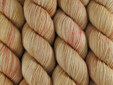 A close up of variegated warm beige tan with coral pink coloured skeins of superwash merino and nylon 4ply fingering sock yarn (Sunburnt on Tough Stocking)