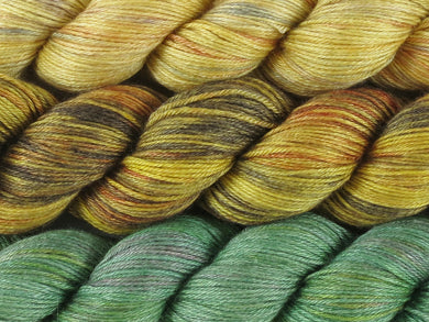A close up of three variegated skeins of yarn from pale yellow with hints of orange, grey and mauve at the top to golden yellow, orange, brown and charcoal in the middle to greens with hints of yellow and pink at the bottom (Sunflowers Stillness MKAL Yarn Kit on Silk Stocking)