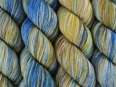 A close up of variegated blue, ecru, milk chocolate and golden yellow coloured skeins of superwash merino and nylon 4ply fingering sock yarn (The Gap on Tough Stocking)