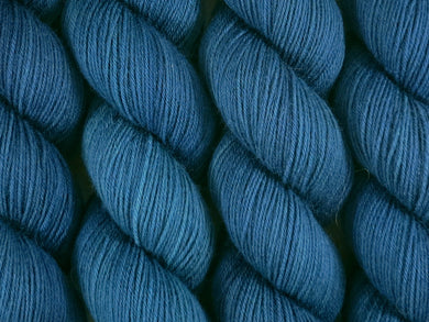 A close up of deep semi-solid blue green, teal and navy with hints of emerald green coloured skeins of superwash merino and nylon 4ply fingering sock yarn (The Kraken Wakes on Tough Stocking)