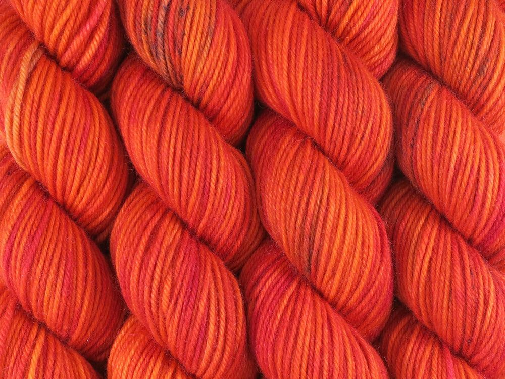 A close up of variegated bright orange, red and fuchsia with black speckles skeins of superwash merino, cashmere and nylon 8ply DK weight yarn (Total Fire Ban on Mother's Love DK)