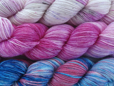A close up of three variegated skeins of yarn from white and pink with purple and black speckles at the top to pink, purple and white in the middle to blues, pink and white at the bottom (Tropical Horizon Impressionists MKAL Yarn Kit on Silk Stocking)