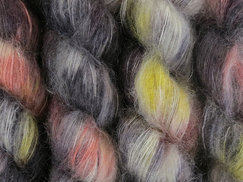 A close up of variegated black, charcoal, silver grey and white with flashes of bright to golden yellow and paprika coloured skeins of superfine kid mohair and silk 2ply lace yarn (Urban Sprawl on Kid Glove Lace)