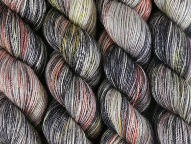 A close up of variegated black, charcoal, silver grey and white with flashes of bright to golden yellow and paprika coloured skeins of superwash merino and silk 4ply fingering sock yarn (Urban Sprawl on Silk Stocking)