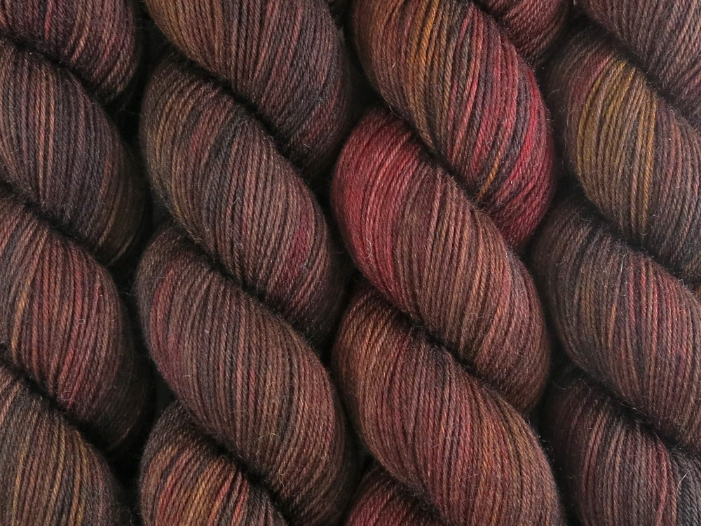 A close up of variegated warm black-brown with hints of golden yellow and rich red coloured skeins of superwash merino and nylon 4ply fingering sock yarn (Vegemite on Tough Stocking)