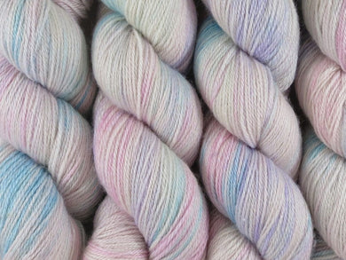 A close up of variegated white, soft pink, blue and violet coloured skeins of superwash bluefaced leicester, silk and cashmere 4ply fingering sock yarn (White Opal on Blue Chip Stocking)