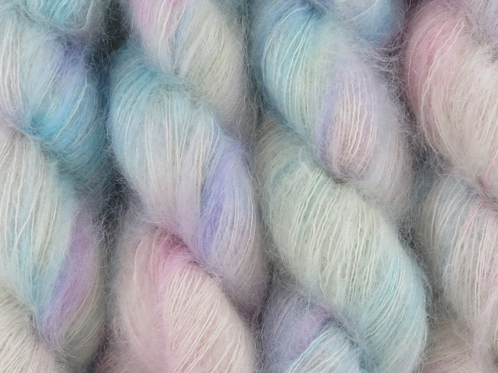 A close up of variegated white, soft pink, blue and violet coloured skeins of superfine kid mohair and silk 2ply lace yarn (White Opal on Kid Glove Lace)