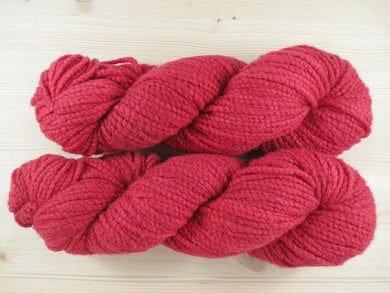 A close up of semi-solid medium red with hints of maroon and crimson coloured skeins of non-superwash Australian merino boucle constructed Aran weight yarn on a pale wooden background (Japonica on White Gum Wool Boucle)