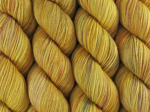 A close up of variegated light golden yellow with hints of rust, maroon and grey coloured skeins of superwash merino and nylon 4ply fingering sock yarn (Yellowblock on Tough Stocking)