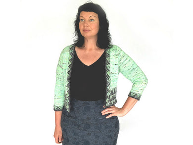 A woman with shoulder length dark hair wearing a black top, grey patterned skirt and a cropped knitted open front jacket in front of a white background. The jacket is a black speckled pale green with dark grey slipped stitch borders along the front and waist bands and three quarter sleeve cuffs
