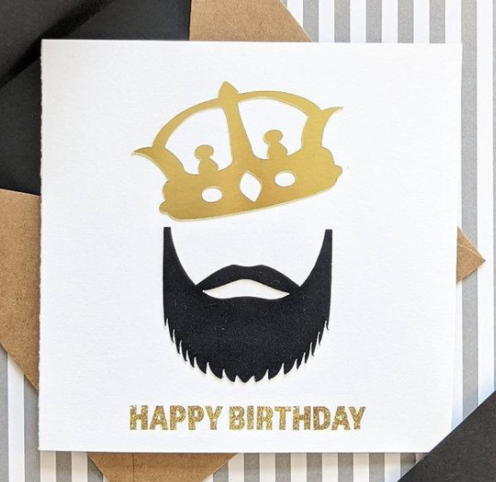 "Your bearded family, friends, and baes will definitely love this card. The front features a metallic paper gold crown along with a velvet textured beard. It gets even better when you open up the card! Not only is there a wonderful message to your bearded king, there's also a definition of ""King"" set atop a background with mini crowns. Whoever you gift this to you will not be disappointed.  5x5 notecard with Kraft envelope"