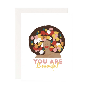 White card with an African American woman on the cover,  with flowers in red, yellow, pink, green and white all in her afro with the words You Are Beautiful