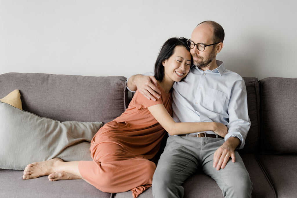 Couple hugging while sitting on a couch
