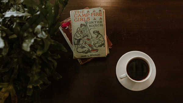 A plant next to a stack of old books and a cup of black coffee on top of an antique coffee table