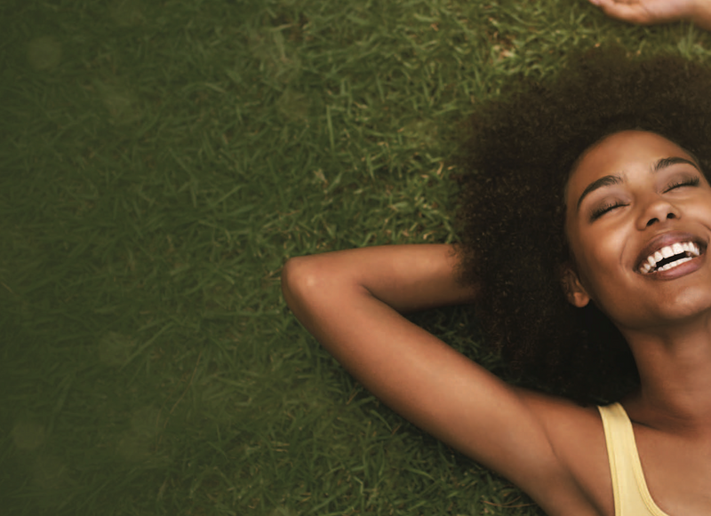 Women laying in a field of grass with her arm folded behind her head.