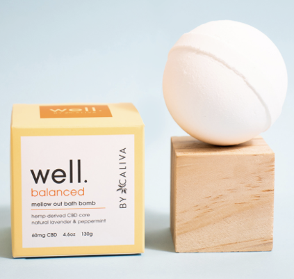 welly by caliva mellow out bath bomb packaging and bath bomb sitting on top of a wooden cube.