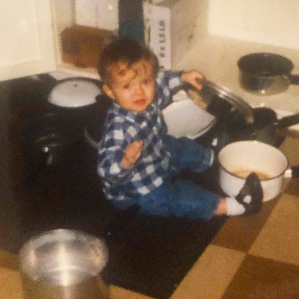 Jack, aged 2, sitting on the kitchen floor playing with pots and pans