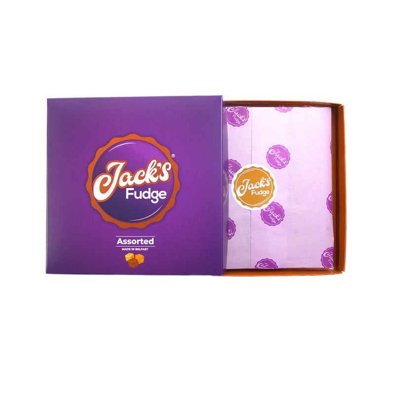 An open gift box of Jack's Assorted fudge. Purple tissue paper with dark purple Jack's Fudge logos is sealed in the middle by a circular brown sticker with Jack's Fudge written across it in white writing.