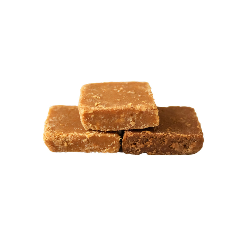 Three squares of crumbly fudge stacked on top of each other in a pyramid shape.