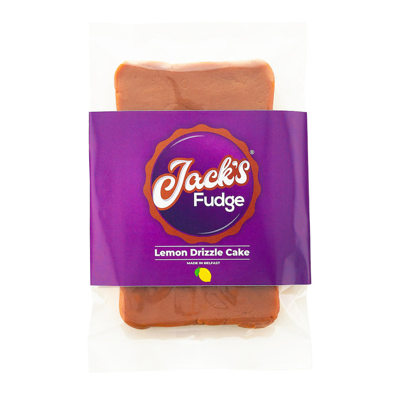Jack's Lemon Drizzle Cake Fudge bar in a clear wrapper. A purple Jack's Fudge sticker across the bar with the Jack's Fudge logo in the middle, 'Lemon Drizzle Cake' written underneath in white writing and a lemon image on the bottom of sticker.