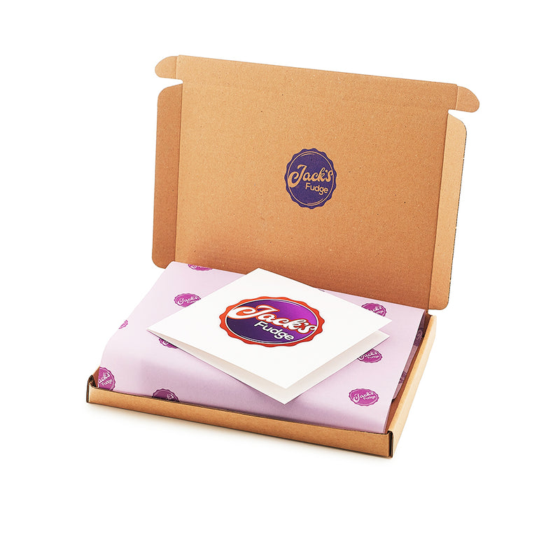 A small, rectangular, brown shipping box open with a purple logo stamped on the inside of the top lid. A white gift card with Jack's Fudge logo sits inside on top of purple tissue paper featuring small, dark purple Jack's Fudge logos across.