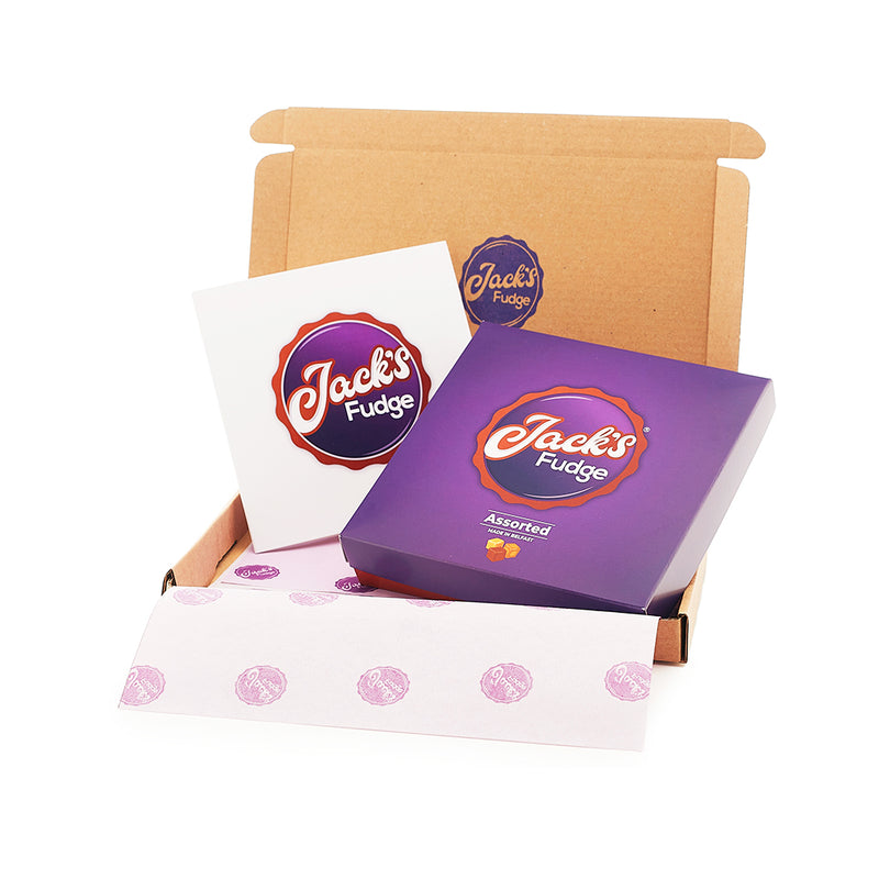 A small rectangular brown open shipping box with a purple Jack's Fudge stamp on the top lid. The bottom of the box is layered with purple tissue with small dark purple Jack's Fudge logos across it. Inside the box is a Jack's Fudge gift box and a white gift card with Jack's Fudge logo on the front of it.