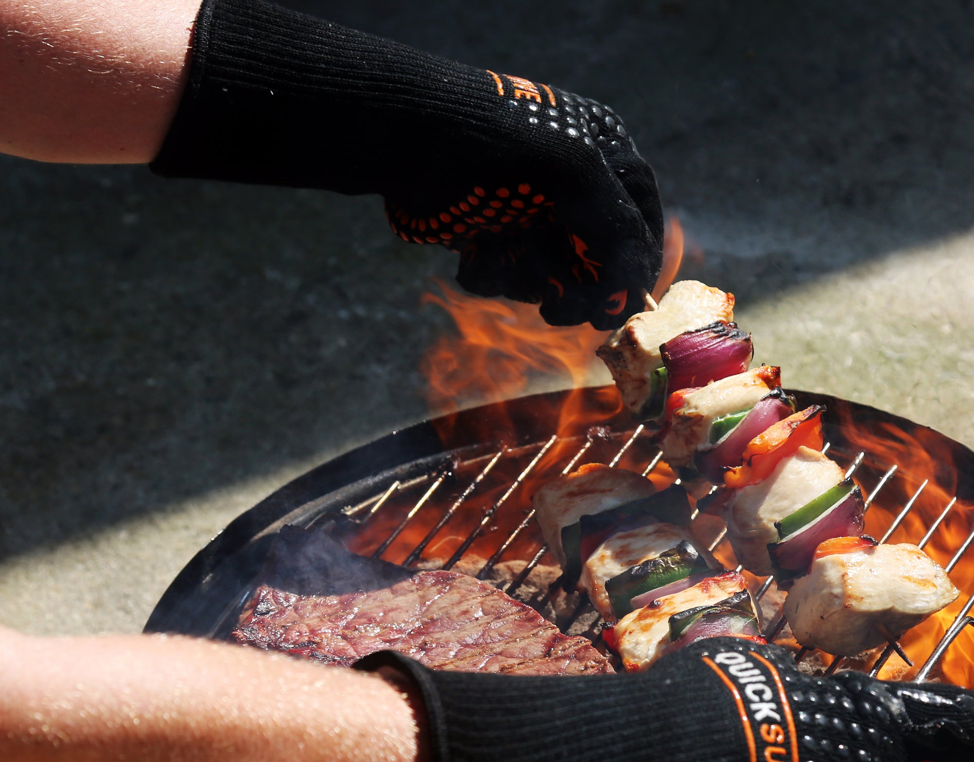 QuickSurvive Heat Resistant Fire Safety Glove picking up burning skewers on the grill - Best gloves for BBQ, Smoking and Grilling. Stop Burning your hands while grilling.