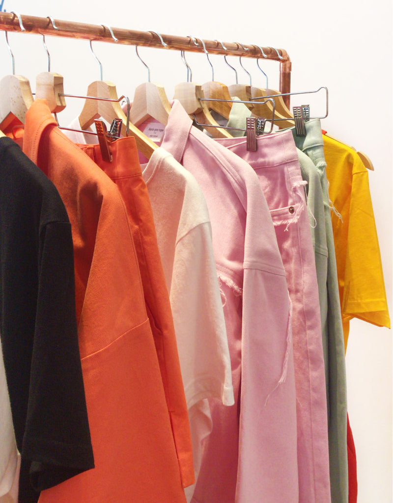 Colourful sustainable upcycled clothing hanging on a rack