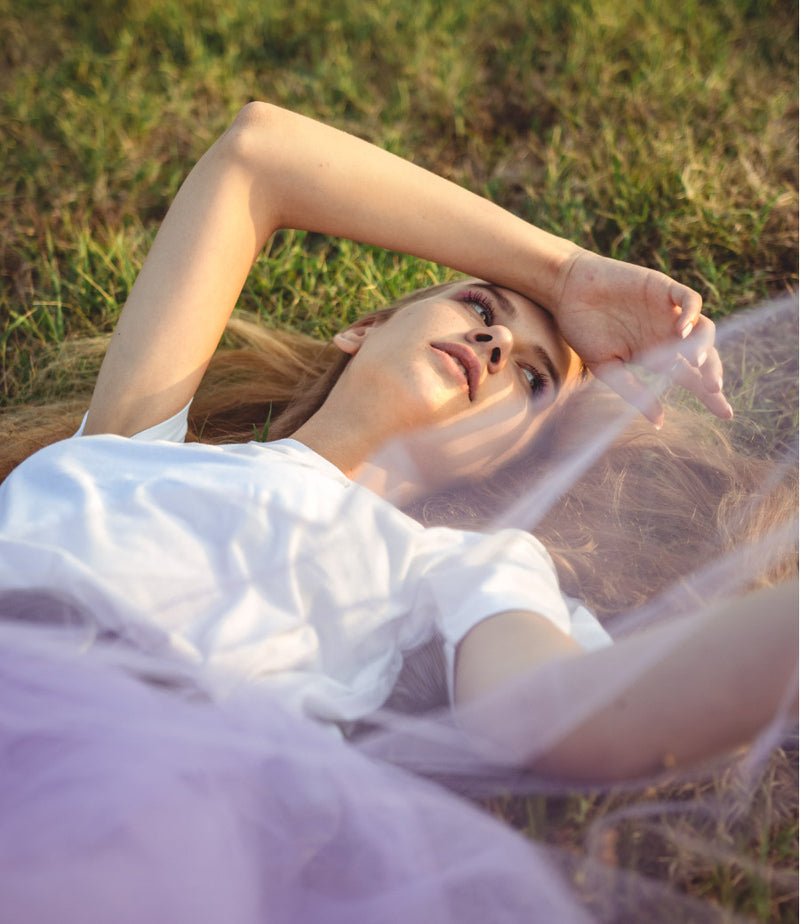 Woman lying on the grass wearing sustainable recycled cotton tee in white and a purple skirt
