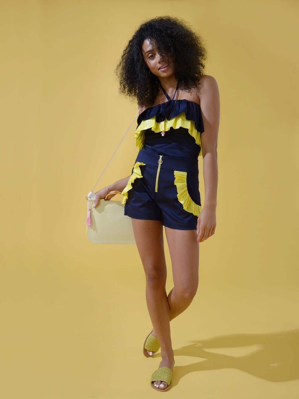 Woman wearing a navy blue strapless halter top with yellow ruffles around the bust and shorts with yellow ruffles around the pockets
